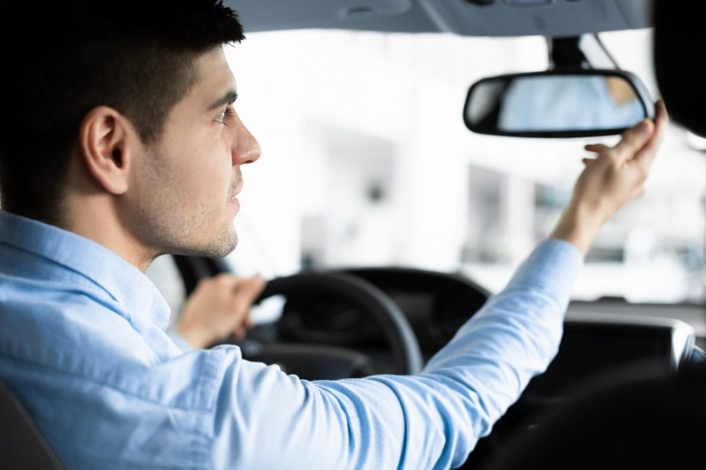 Guy Checking Mirrors Sitting In Driver's Seat
